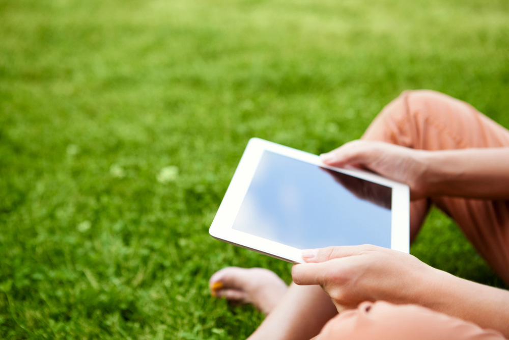 Woman holding a digital tablet and sitting on the grass